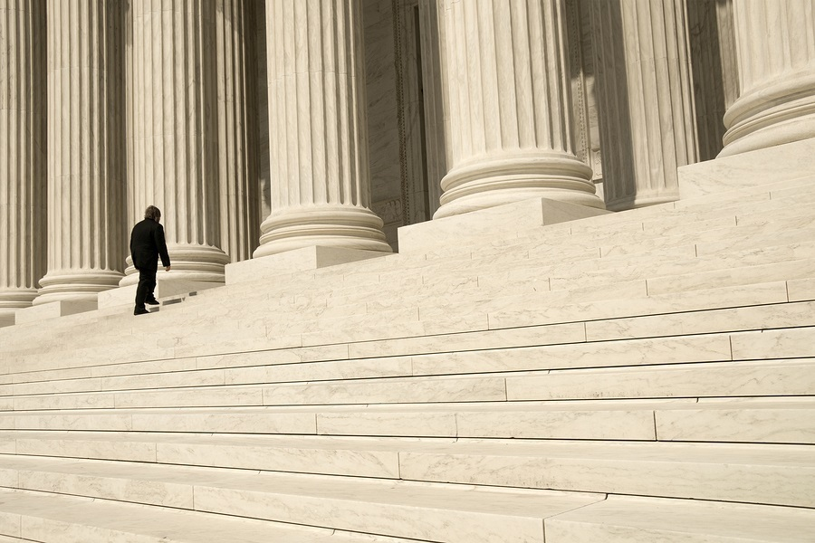 A man ascending the steps at the entrance to the US Supreme Court in Washington DC.