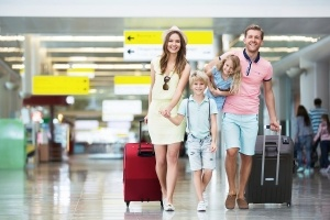 Happy-family-with-suitcases-in-airport-300x200
