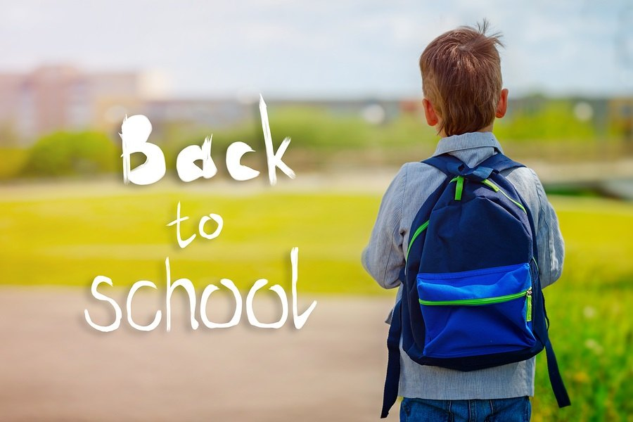 Child going back to school with backpack on green nature background with text Back to school. Back view.