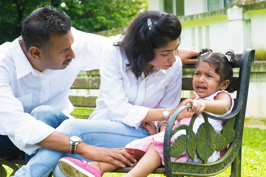 Indian family outdoor. Parents is comforting their crying daughter.