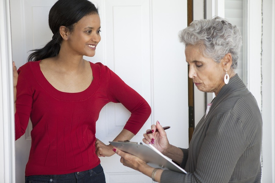 Black woman greeting a solicitor at her front door photo