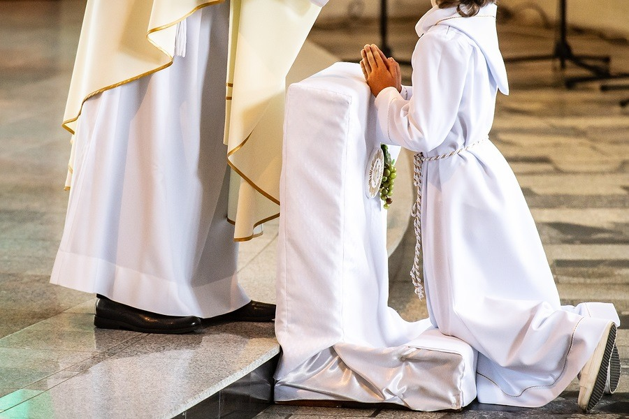 boy on his knees accepting first holy communion