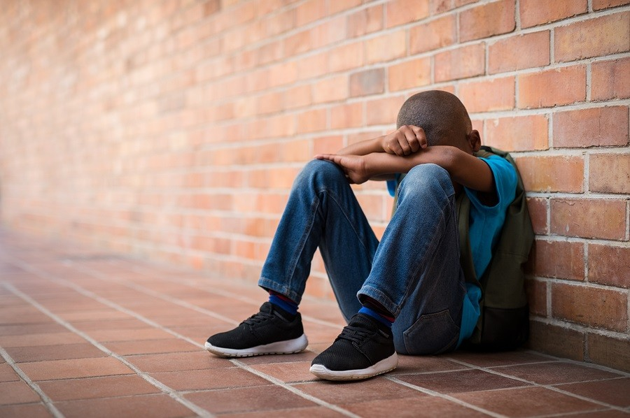 Young boy sitting alone with sad feeling at school.