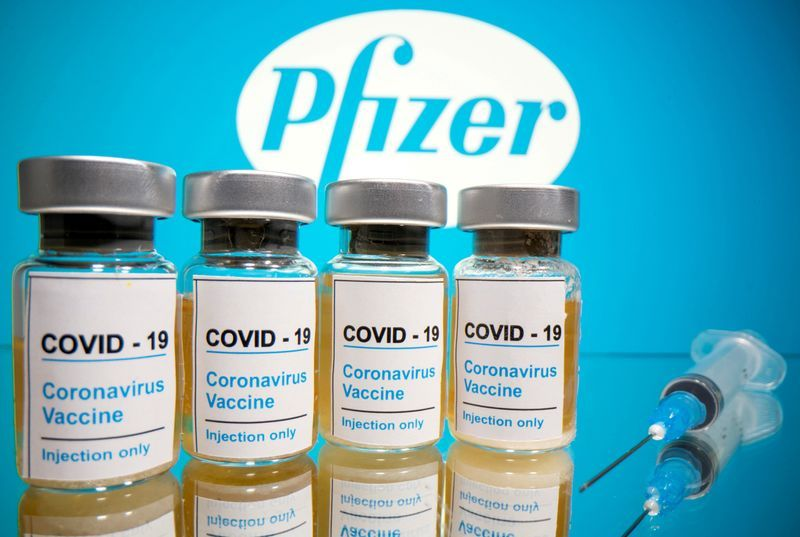 """FILE PHOTO: Vials with a sticker reading, """"COVID-19 / Coronavirus vaccine / Injection only"""" and a medical syringe are seen in front of a displayed Pfizer logo in this illustration taken October 31, 2020. REUTERS/Dado Ruvic/Illustration"""